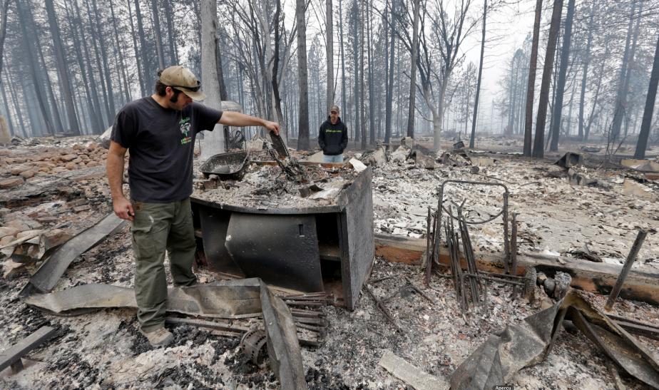 Adam Bailey fouille parmi les débris de sa maison avec son beau-père Joel Miller, le lundi 14 septembre, à Cobb, en California. Bailey a échappé aux flammes avec son bébé, samedi, juste avant que ne s'embrase son quartier d'une douzaine de maisons. | 14 septembre 2015
