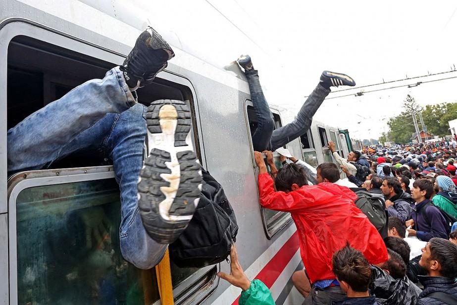 Des migrants se bousculent pour monter à bord... (PHOTO AFP)