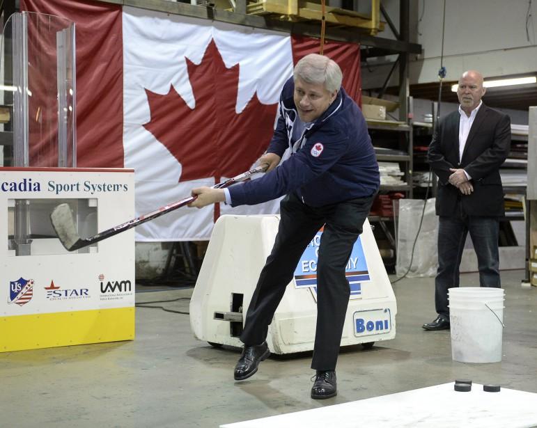 Stephen Harper tente un tir au but lors d'un arrêt dans une usine qui fabrique de l'équipement de hockey, à Port Moody, en Colombie-Britannique, le 15 septembre. (La Presse Canadienne)