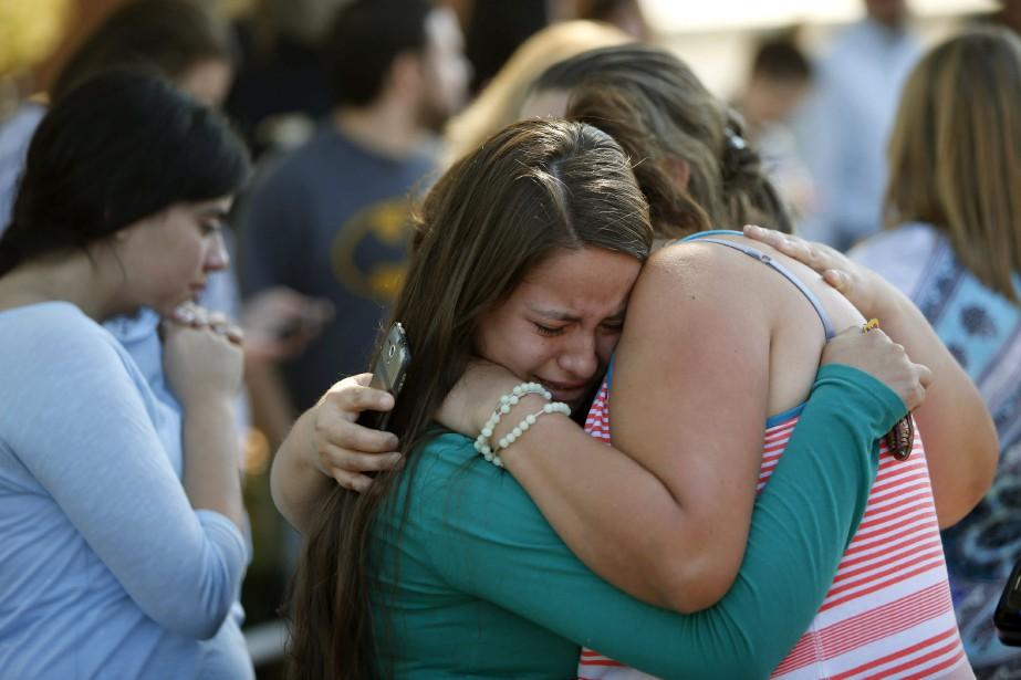 Une mère serre dans ses bras sa fille... (Photo Andy Nelson, The Register-Guard/AP)