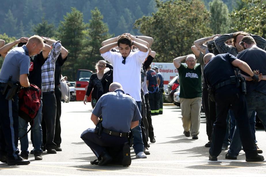 Les policiers fouillent les étudiants de l'Umpqua Community... (PHOTO MIKE SULLIVAN, ROSEBURG NEWS-REVIEW/AP)