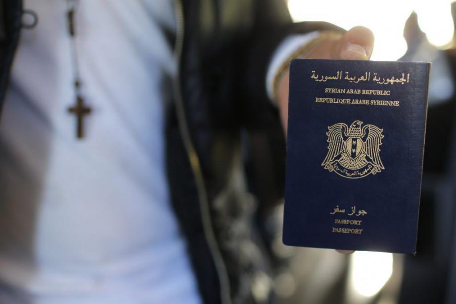 Un Syrien montre son passeport à son arrivée... (PHOTO STEPHANE MAHE, REUTERS)