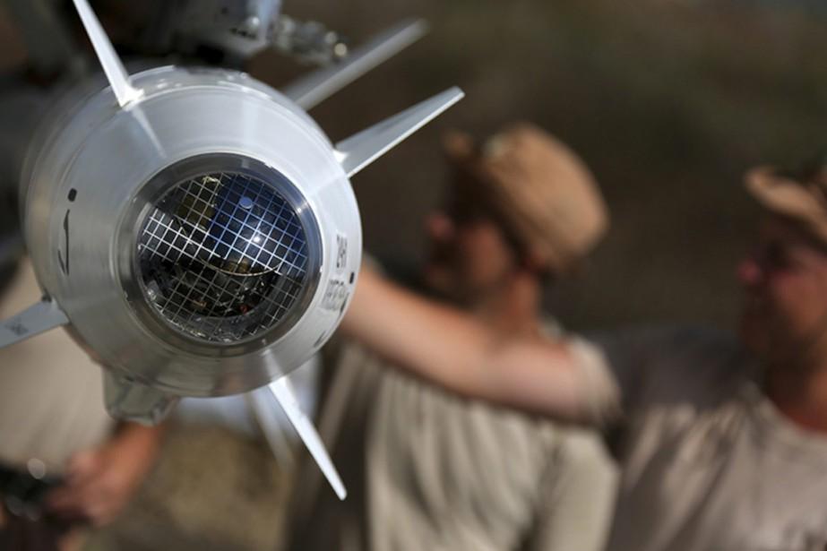 Des techniciens militaires russes installent un missile sur... (Photo AP)