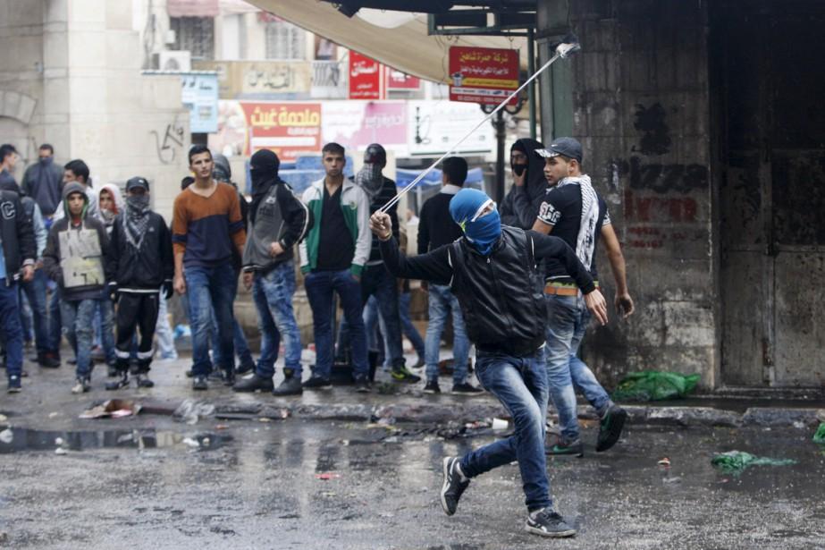 Un jeune Palestinien utilise un lance-pierre lors d'un... (PHOTO MUSSA QAWASMA, ARCHIVES REUTERS)