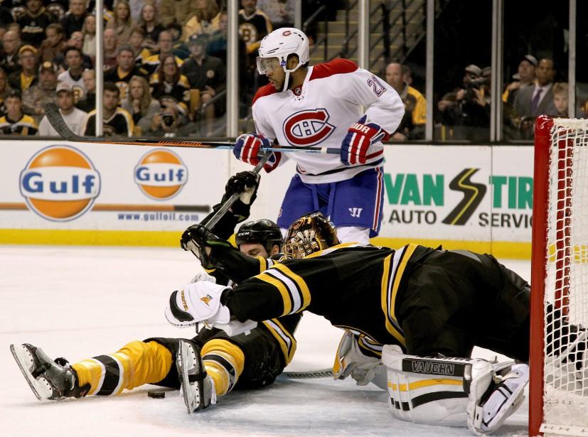 Tuukka Rask veut mettre la main sur la rondelle entre les jambes d'Adam McQuaid. (PHOTO MARY SCHWALM, AP)