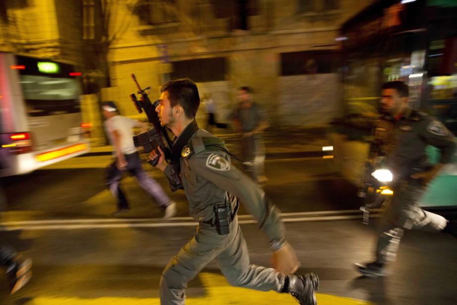 Des policiersdes forces spéciales courent après un homme... (PHOTO DUSAN VRANIC, AP)