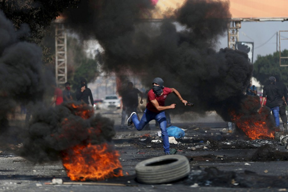 Un Palestinien lance une pierre en direction de... (PHOTO AHMAD TALAT, REUTERS)
