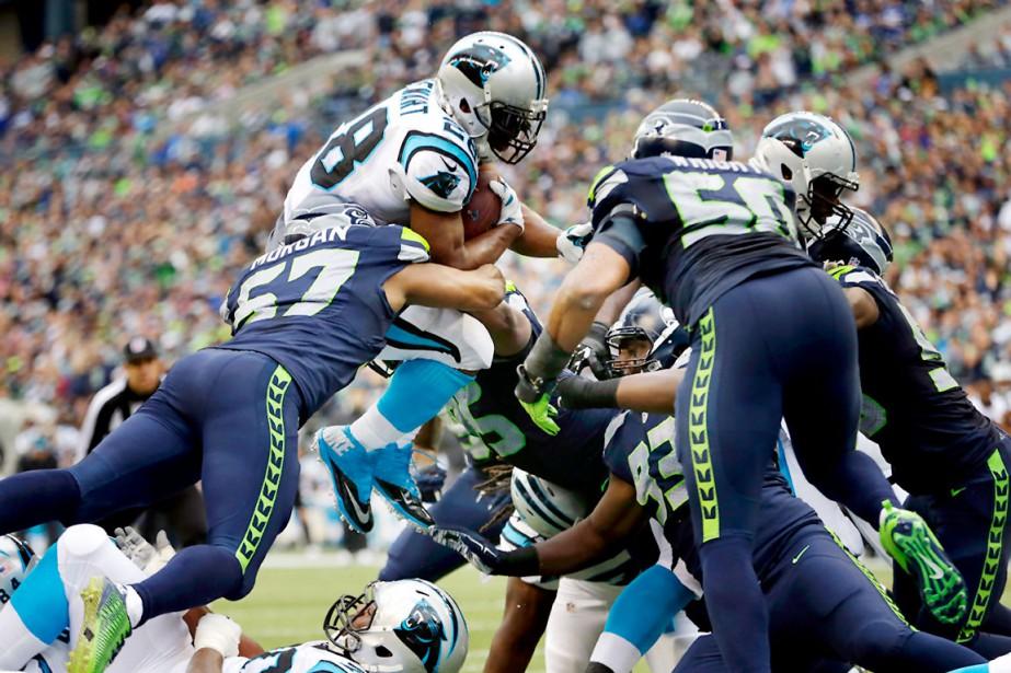 Le demi-offensif des Panthers de la Caroline, Jonathan Stewart, a bondi par-dessus Mike Morgan, le secondeur extérieur des Seahawks de Seattle, pour marquer un touché lors de la deuxième demie du match. Les Panthers ont battu les Seahawks 27-23. (AP, Elaine Thompson)