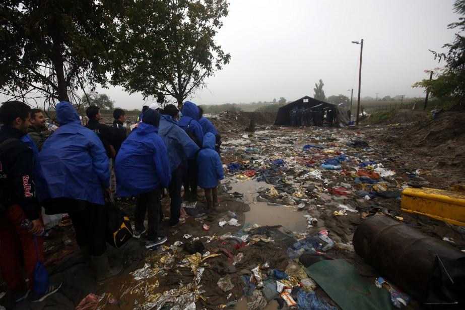 Des migrants attendent de pouvoir traverser la frontière... (PHOTO DARKO VOJINOVIC, ASSOCIATED PRESS)