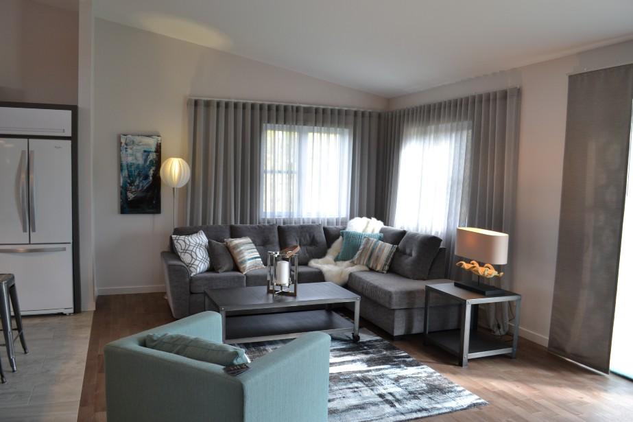 Les meubles fournis par Gagnon Frères se fondent parfaitement dans le décor. Seule touche de couleur, le aqua que l'on retrouve sur le fauteuil, le tapis ainsi que dans les toiles de l'artiste peintre Édith Privé. ()