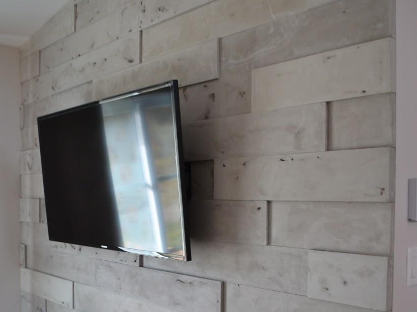 Derrière le téléviseur, un mur de béton avec jeu de profondeur. ()