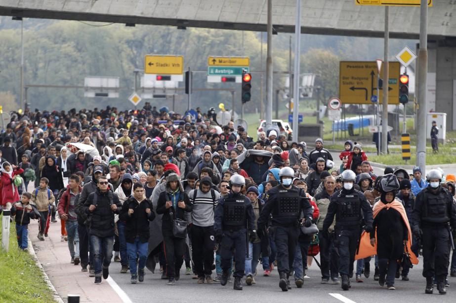 Des policiers escortent un groupe de migrants arrivés... (Photo Petr David Josek, AP)