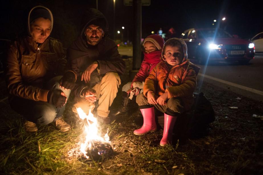 Une famille tente de se réchauffer après avoir... (PHOTO VLADIMIR SIMICEK, AFP)