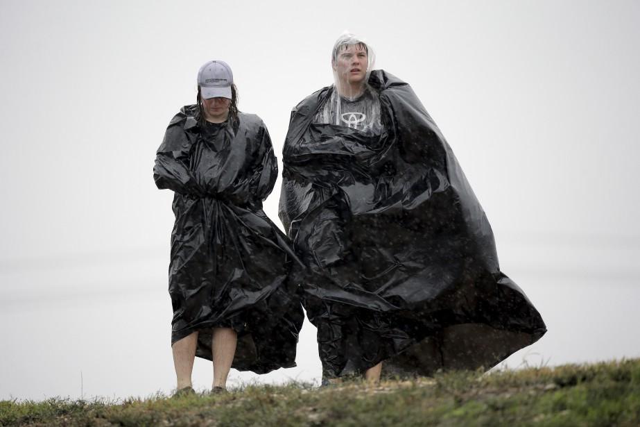 Le froid et la pluie n'épargnent pas les irréductibles spectateurs. (Photo AP, Eric Guay)