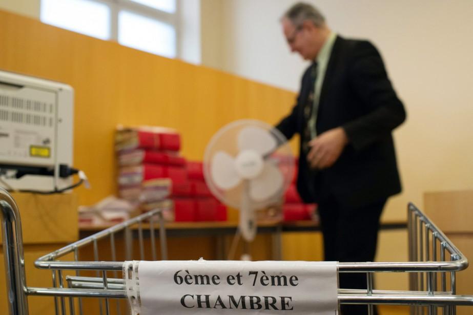 Un homme dépose des documents relatifs au dossier... (PHOTO BERTRAND LANGLOIS, AFP)