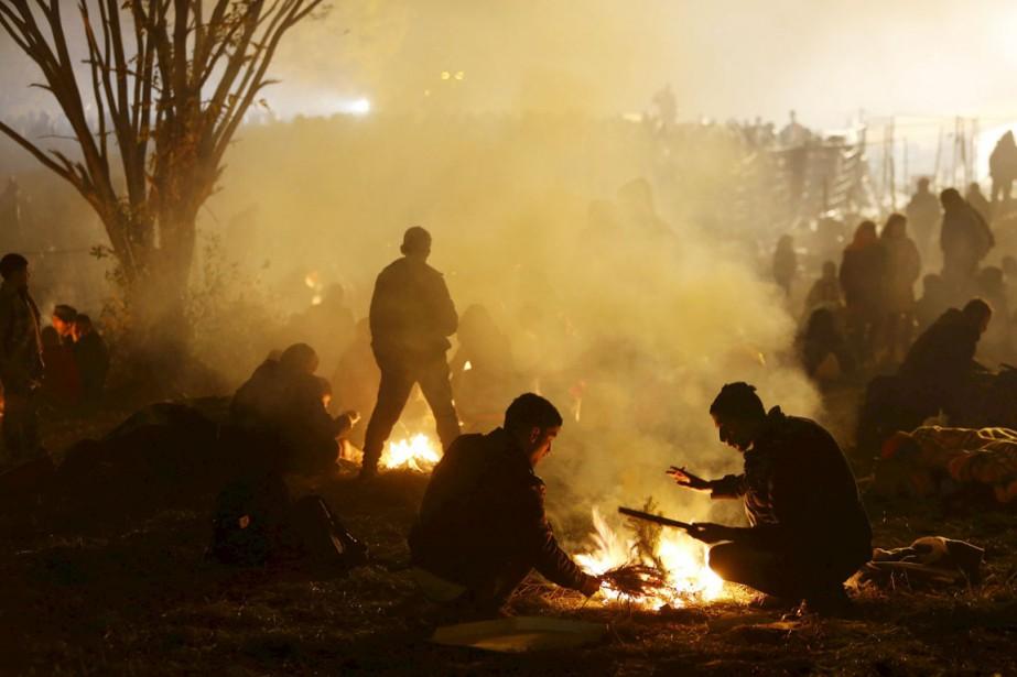 Migrants et réfugiés tentent de se réchauffer tant... (PHOTO SRDJAN ZIVULOVIC, REUTERS)