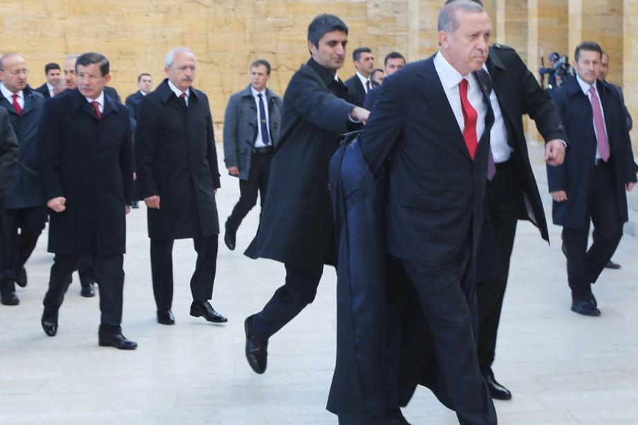 Un assistant enlève le manteau du président Erdogan,... (PHOTO ADEM ALTAN, ARCHIVES AFP)