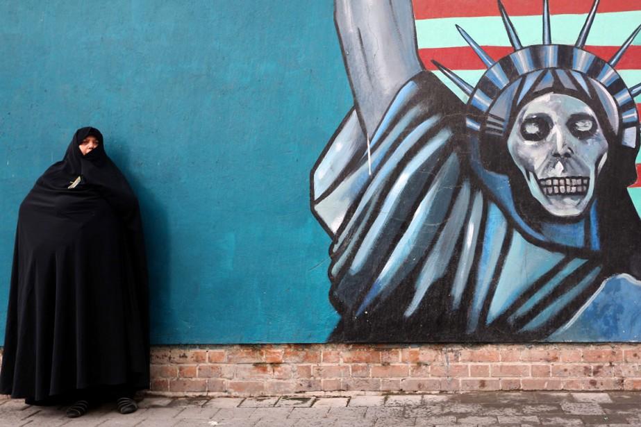 Une Iranienne se fait photographier devant un graffiti... (PHOTO ATTA KENARE, ARCHIVES AFP)