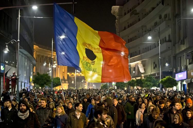 Certains manifestants portaient le drapeau roumain troué, symbole... (PHOTO AP)