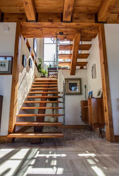 L'escalier est composé de pièces de pin massif, de verre trempé et de fer forgé patiné à l'ancienne. Au rez-de-chaussée, la plage de l'escalier est quant à elle formée de pierres de rivière et de ciment. (Courtoisie Édith Harvey)