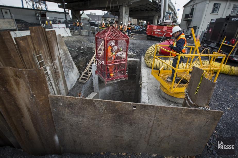 À bord d'une nacelle, deux travailleurs descendent dans... (PHOTO OLIVIER PONTBRIAND, LA PRESSE)