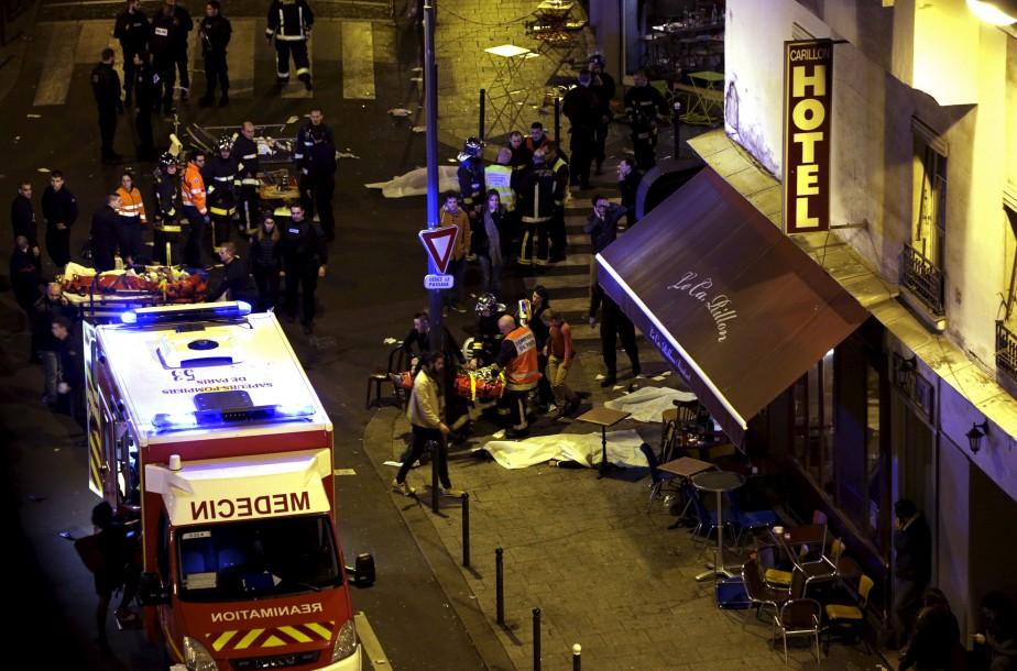 Du personnel médical vient en aide à des victimes alors que des corps jonchent le sol près d'un restaurant, peu après les attentats.  | 13 novembre 2015