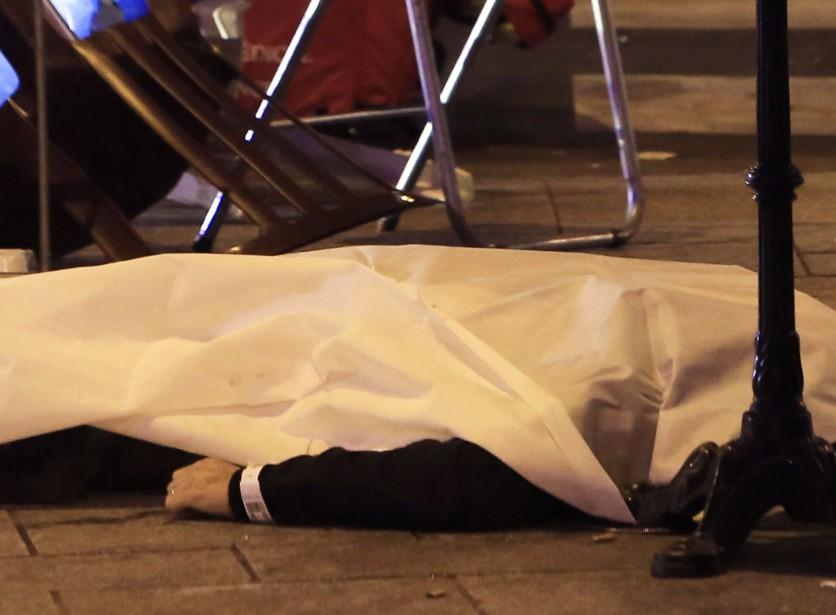 Une victime repose sur le pavé, près de l'entrée d'un restaurant de Paris.  | 13 novembre 2015