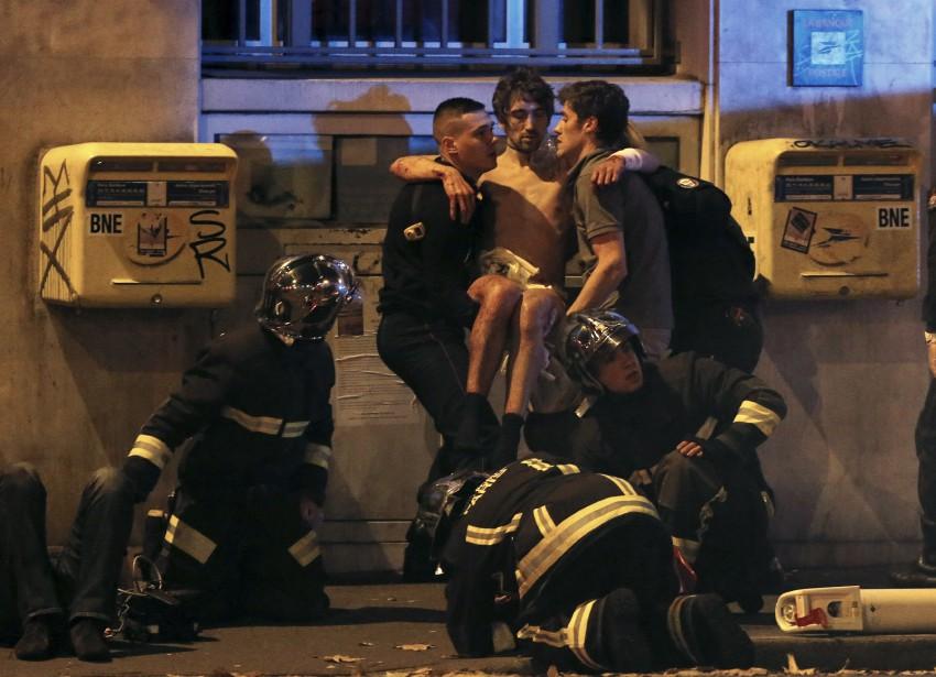 Des pompiers viennent en aide à un blessé, près de la salle de spectacle Le Bataclan peu après les attentats.  | 13 novembre 2015