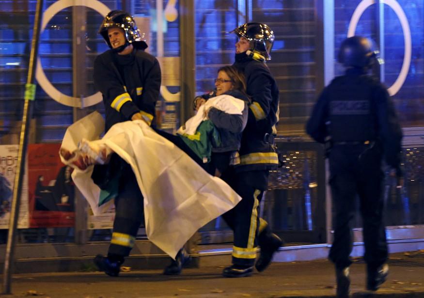 Des pompiers viennent en aide à une dame blessée, près de la salle de spectacle Le Bataclan peu après les attentats.  | 13 novembre 2015