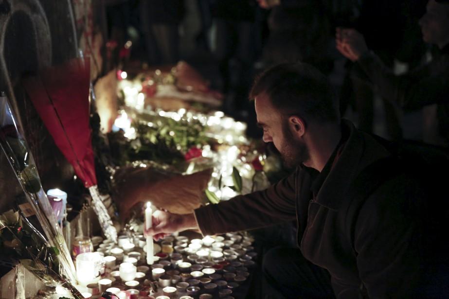 UN homme allume un lampion en hommage aux victime des attentats à la Place de la République. | 14 novembre 2015