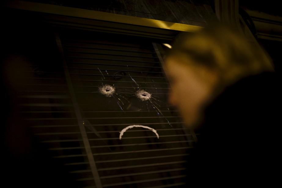 Deux trous de balles transformées en visage triste, dans la vitrine du restaurant Belle Équipe. | 14 novembre 2015