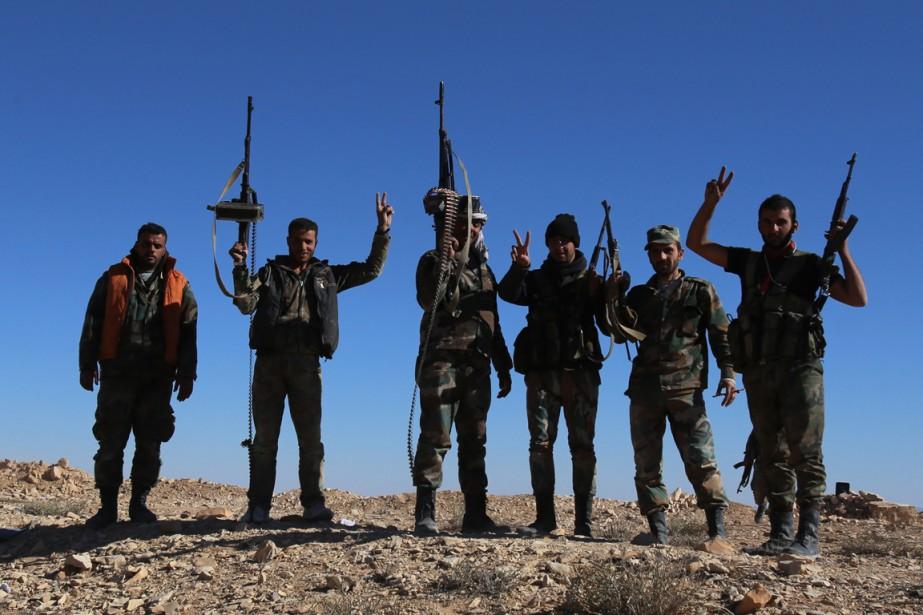 Des forces pro-gouvernementales font le signe de la... (Photo YOUSSEF KARWASHAN, AFP)