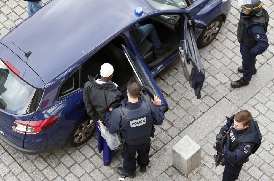 Un suspect est emmené par les policiers à l'issue du raid visant un appartement dit «conspiratif» de la proche banlieue parisienne où se situe notamment le Stade de France. (PHOTO FRANÇOIS MORI, AP)