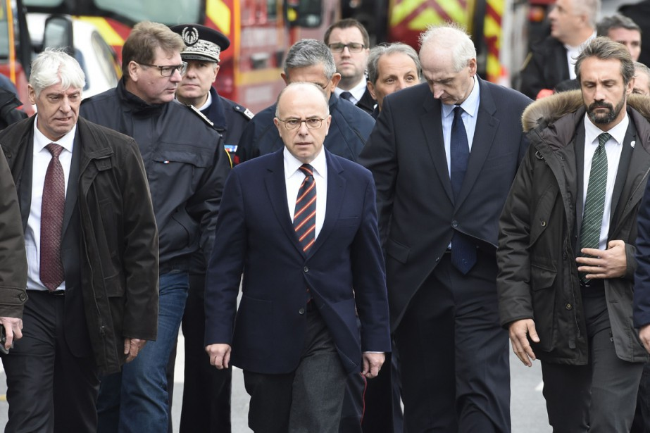 Le ministre de l'Intérieur Bernard Cazeneuve (au centre) arrive sur les lieux du raid, à Saint-Denis, le 18 novembre. (PHOTO LIONEL BONAVENTURE, AFP)
