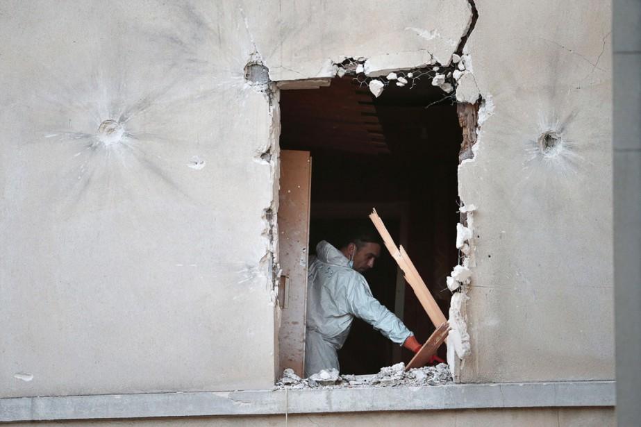 Un expert en criminalistique passe au peigne fin l'appartement où a eu lieu le raid des forces françaises, à Saint-Denis, le 18 novembre. (PHOTO  JOEL SAGET, AFP)