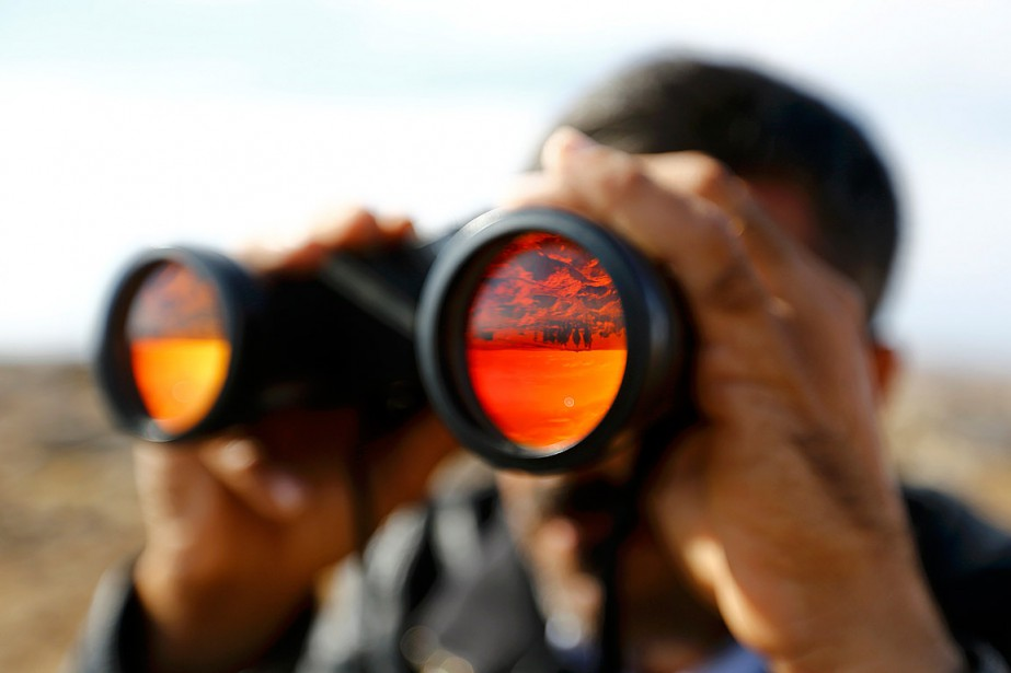 Un Kurde regarde à travers des longues-vues vers... (Photo Kai Pfaffenbach, archives Reuters)