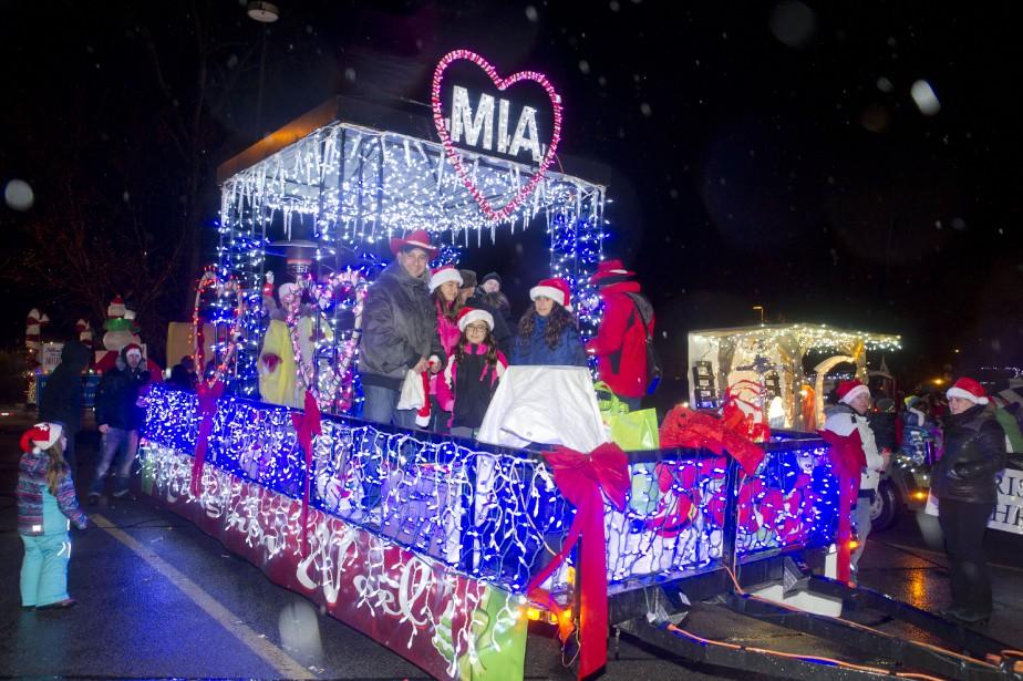 Plusieurs familles ont affronté la pluie afin d'accueillir le père Noël et ses chars allégoriques, vendredi soir, dans le secteur Aylmer. (Martin Roy, LeDroit)
