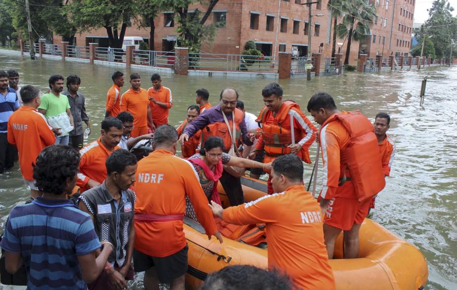 Des centaines de soldats, pompiers, policiers et autres secouristes ont évacué les gens coincés chez eux par les eaux. (AP)