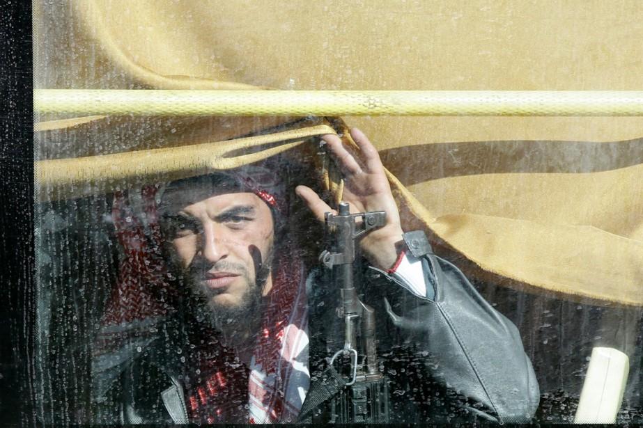 Un rebelle syrien, l'arme à la main, regarde... (PHOTO LOUAI BESHARA, ARCHIVES AFP)