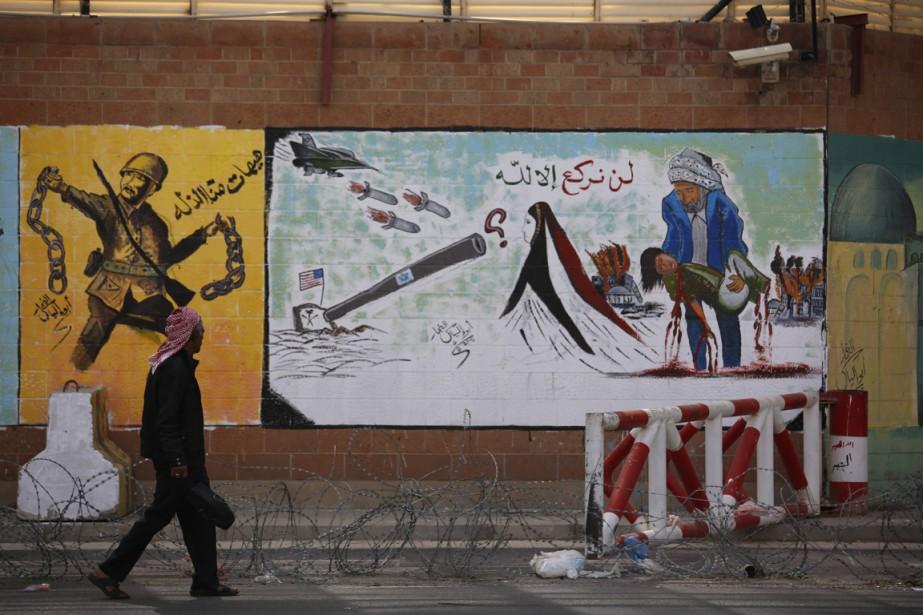 Un homme passe devant des graffes anti-saoudiens et... (Photo Hani Mohammed, AP)