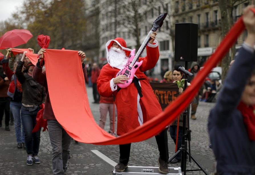 À côté de l'Arc de Triomphe, une longue banderole de tissu rouge a été déployée tout le long de l'avenue de la Grande Armée par des manifestants portant des vêtements et accessoires rouges et tenant à la main une fleur ou un parapluie de la même couleur pour marquer la fin de la conférence sur le climat. (AP, Matt Dunham)