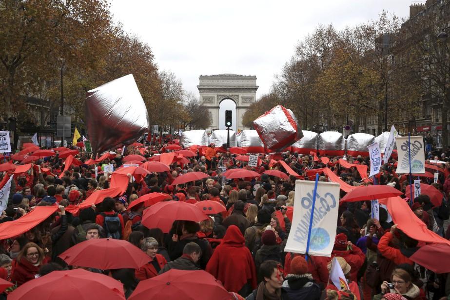 À côté de l'Arc de Triomphe, une longue banderole de tissu rouge a été déployée tout le long de l'avenue de la Grande Armée par des manifestants portant des vêtements et accessoires rouges et tenant à la main une fleur ou un parapluie de la même couleur pour marquer la fin de la conférence sur le climat. (AP, Thibault Camus)