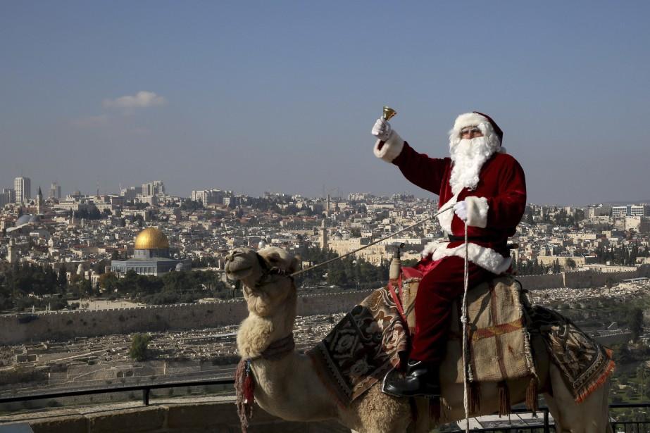 Un Palestinien chrétien déguisé en père Noël se promène à dos de chameau sur le mont des Oliviers, à Jérusalem, le 21 décembre. (AFP, Gali Tibbon)
