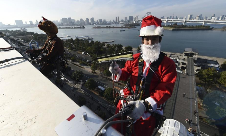Des laveurs de vitres déguisés en père Noël et en renne effectuent leur travail sur un centre commercial de Tokyo. (AFP, Toshifumi Kitamura)