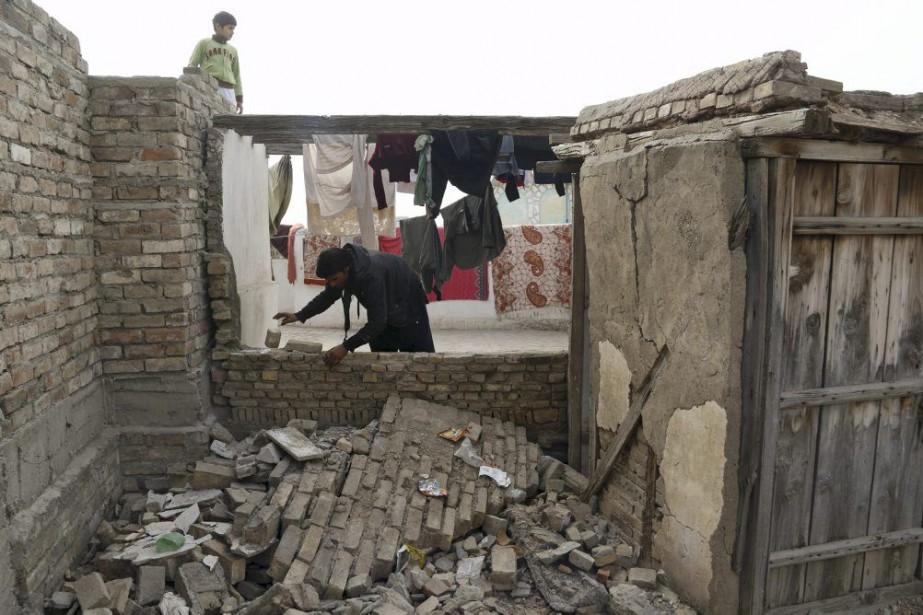 Un homme vérifie l'étendue des dommages sur un... (PHOTO KHURAM PARVEZ, REUTERS)
