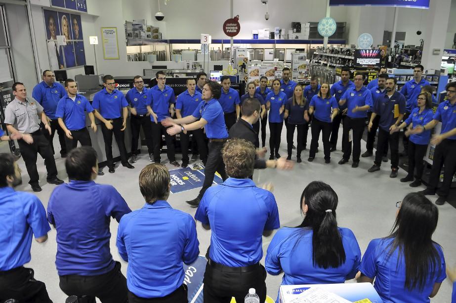 Installés devant l'entrée du magasin, les employés du Best Buy de Place du royaume ont dansé, tapé des mains et chanté, avant d'affronter le quart de travail le plus intense de l'année. (Photo Le Progrès-Dimanche, Rocket Lavoie)