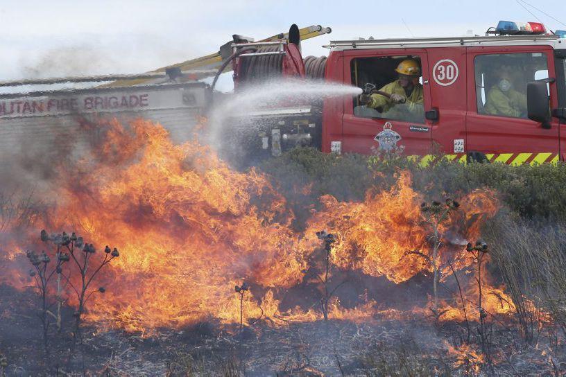 Des pompiers tentent d'éteindre un feu dans la... (PHOTO DAVID CROSLING, REUTERS/AAP)