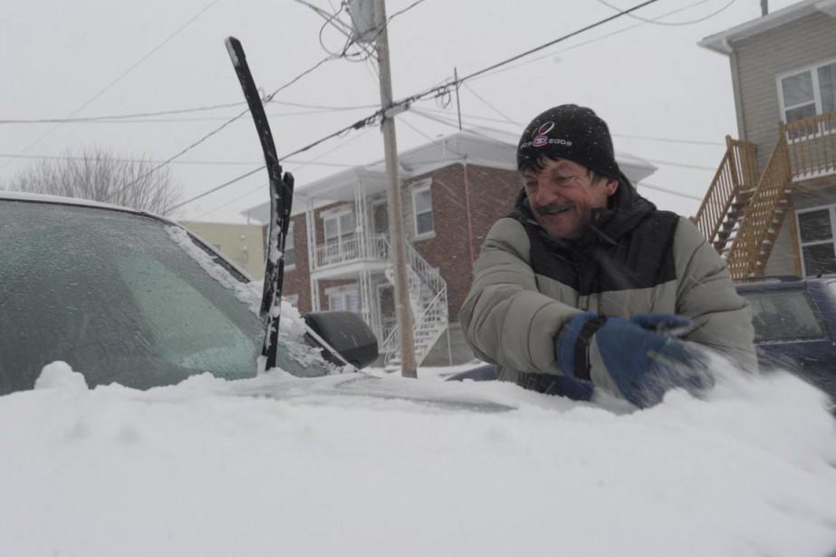 À défaut d'un balais à neige, M. Mc Murray du secteur Shawinigan-Sud n'a eu d'autre choix que d'utiliser ses mains pour chasser l'épaisse couche de neige qui recouvrait son véhicule. (Sylvain Mayer)