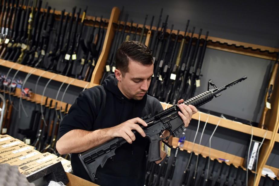 Un employé inspecte un fusil d'assault, dans un... (Photo JEWEL SAMAD, AFP)