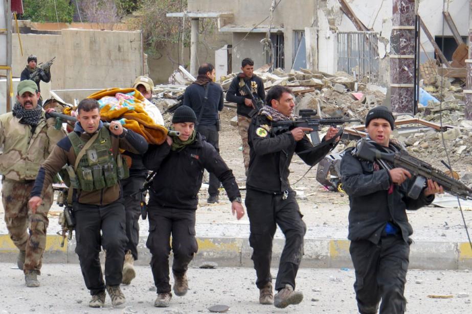 Des membres de forces de sécurité irakiennes évacuent... (PHOTO ARCHIVES AFP)